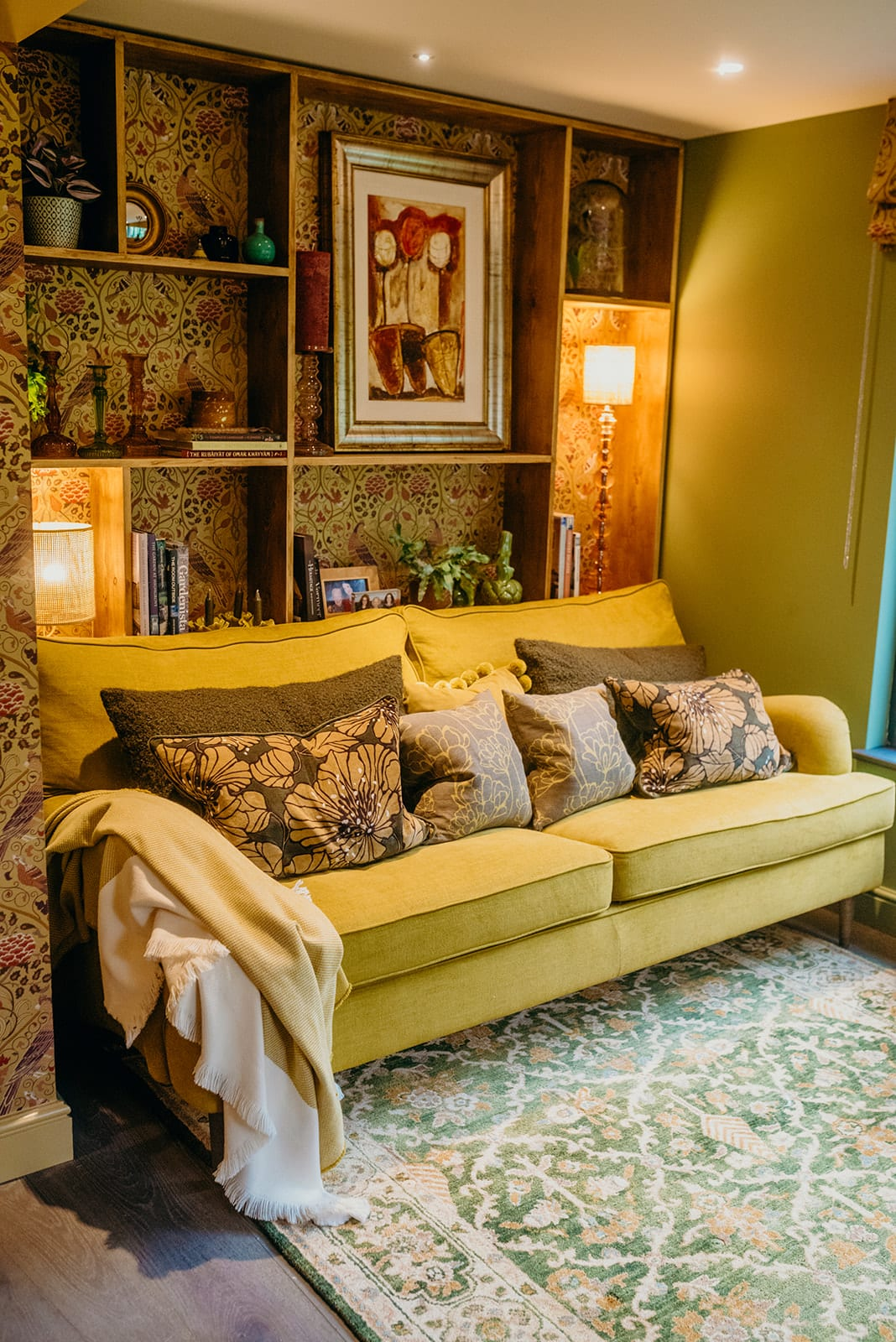 country house living room mustard sofa cushions bookcase William Morris wallpaper