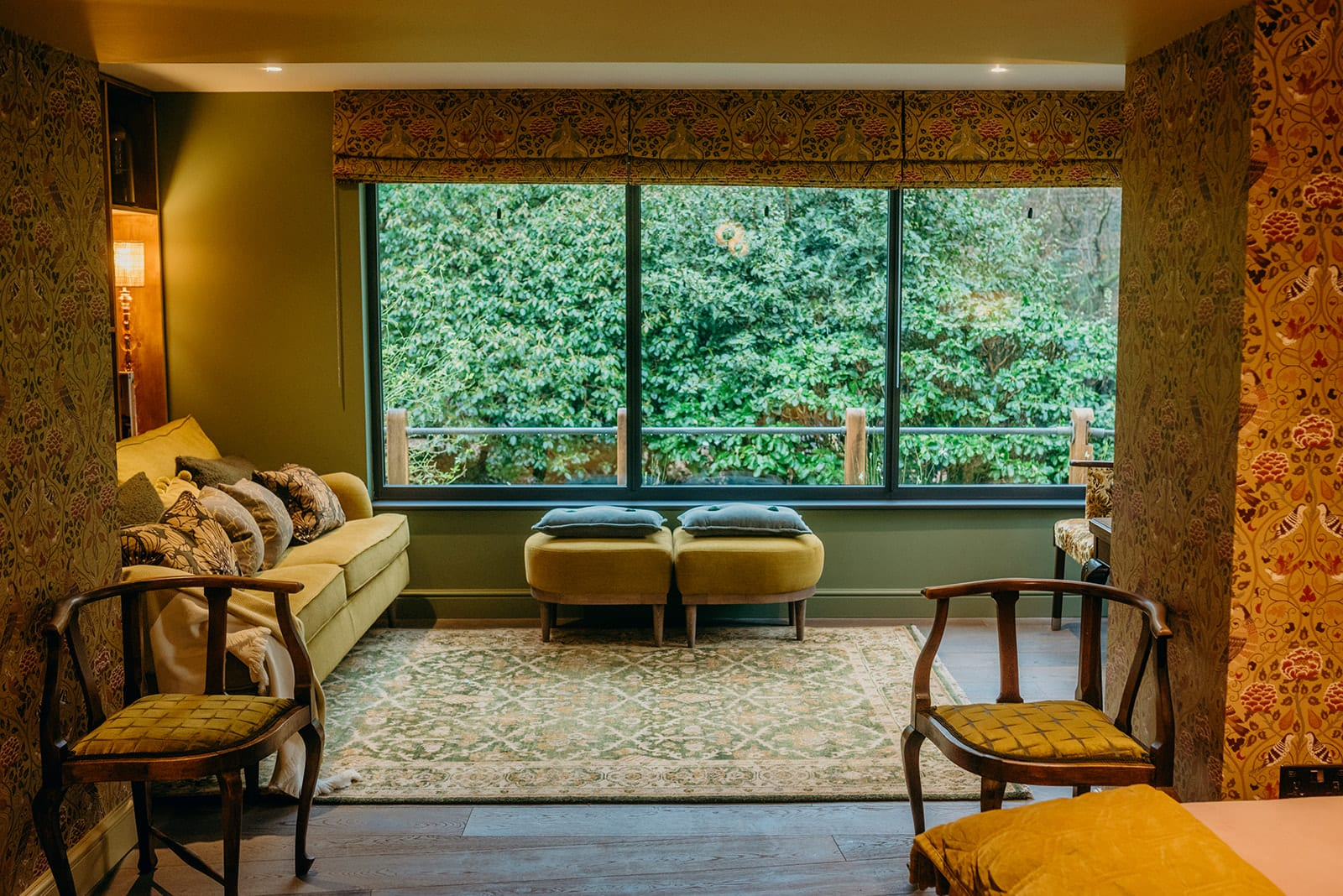 country house living room green rug William Morris wallpaper mustard sofa wood floor