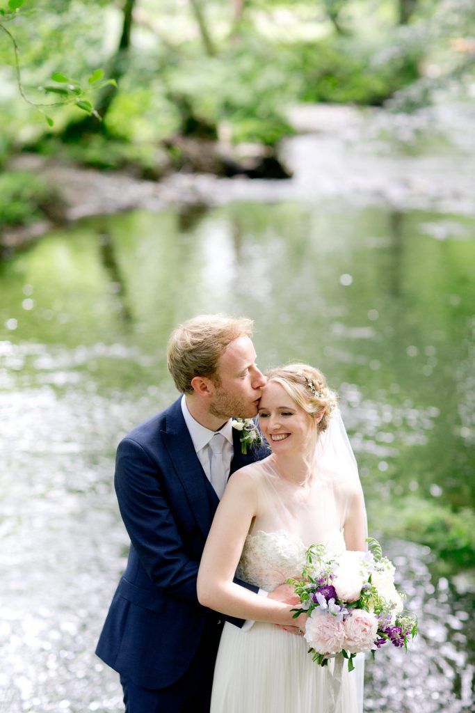 groom kissing bride dartmoor river backdrop