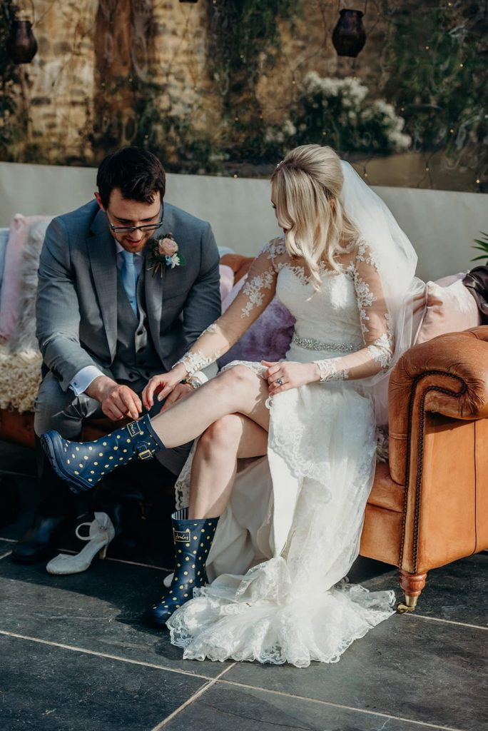 groom helping bride with boots
