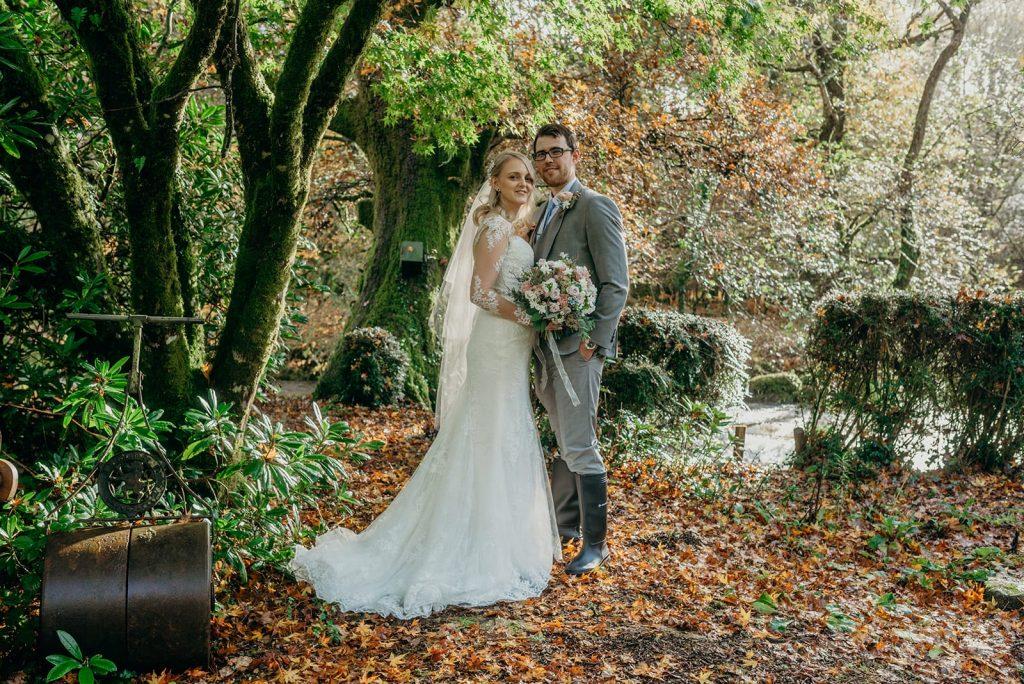 bride and groom posing under autumn tree