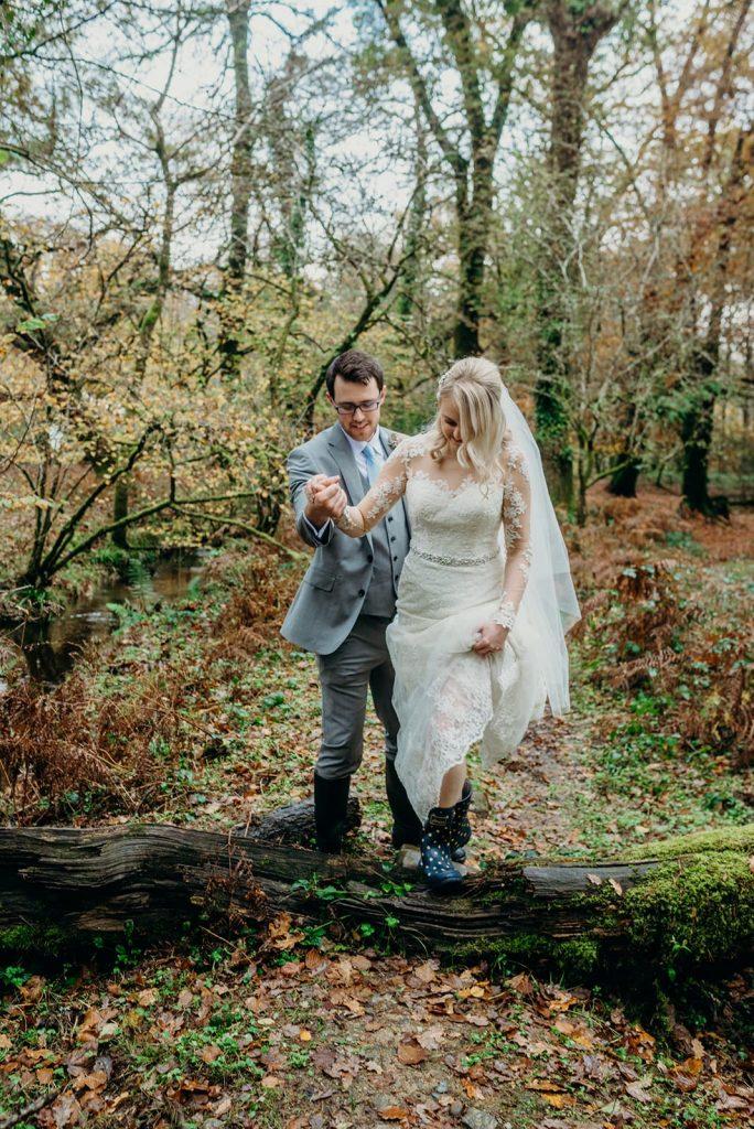 groom helping bride over fallen tree in forest