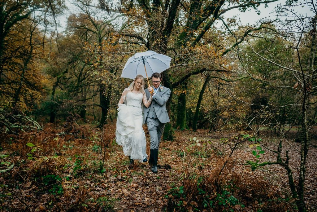 bride and groom walking in autumn woodland with umbrella