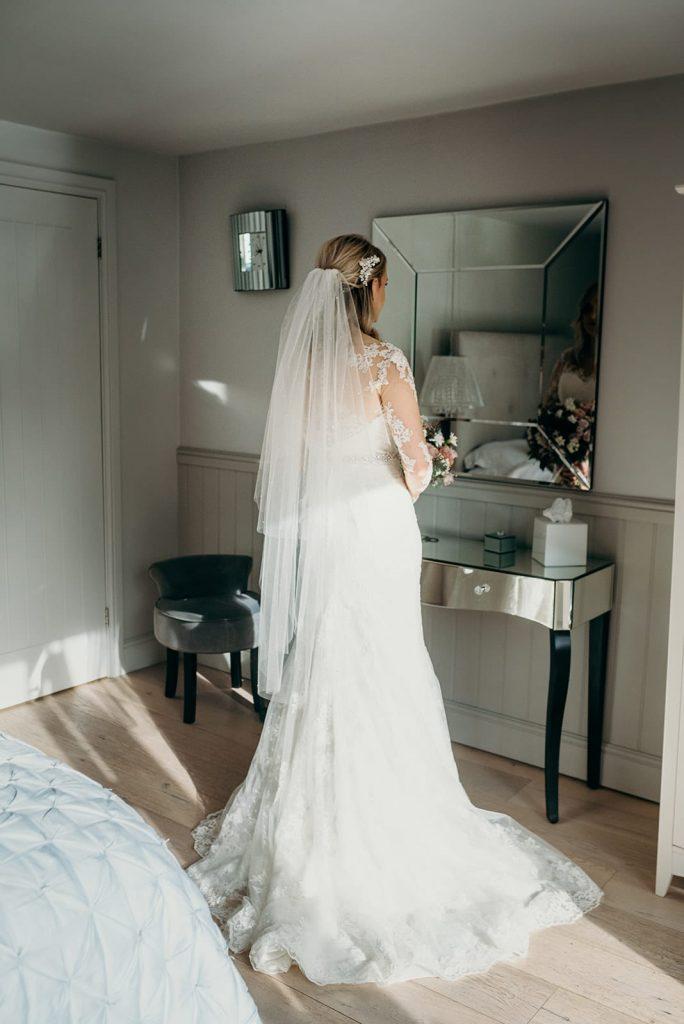 rear shot of bride looking in mirror