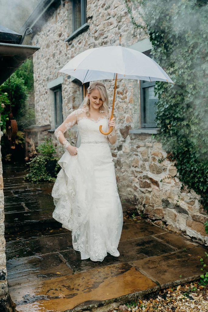 bride walking into wedding ceremony with white umbrella