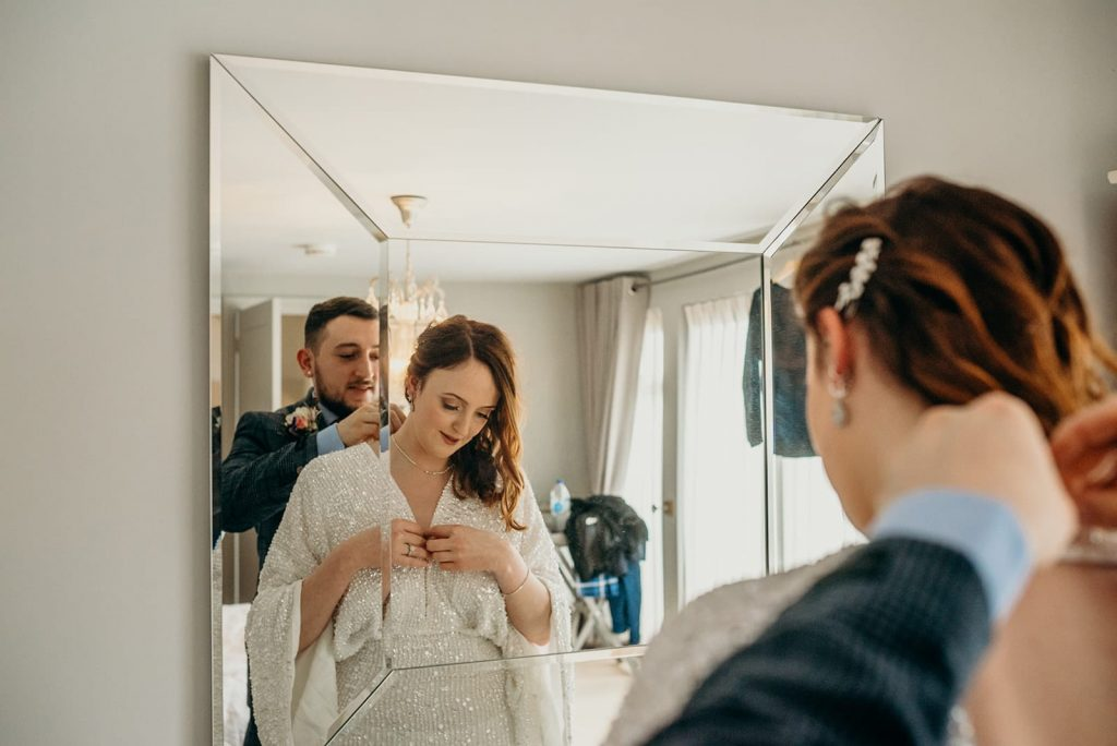 groom putting on brides necklace