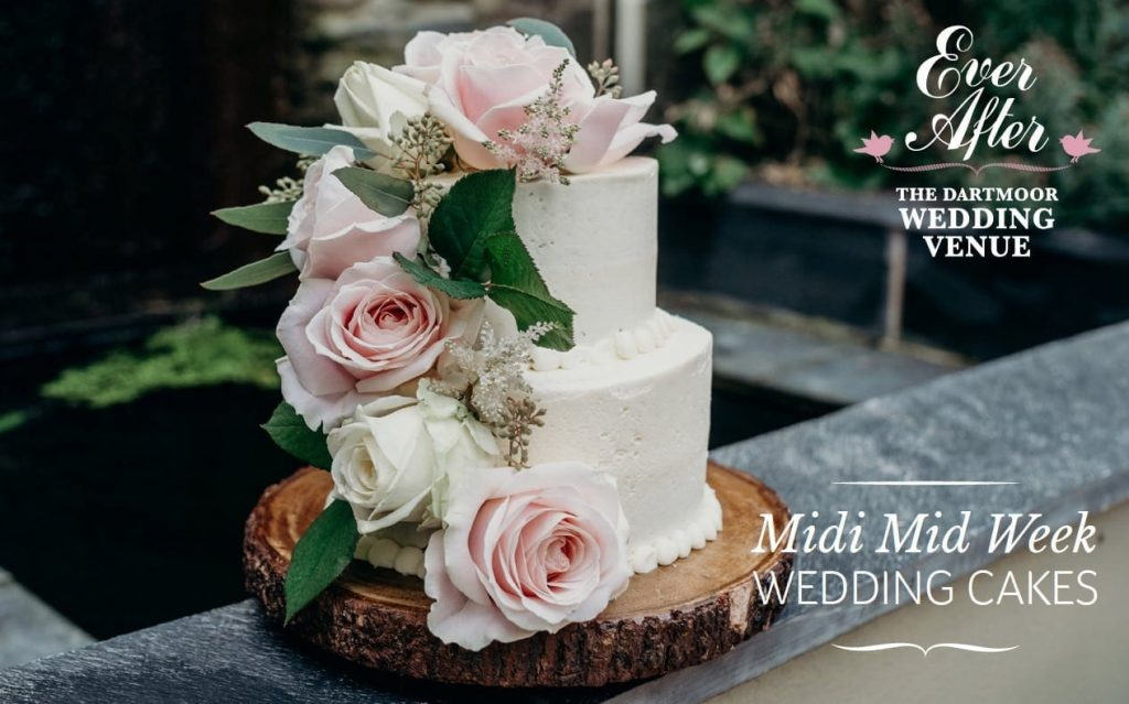 small wedding cake on log slice with blush pink roses