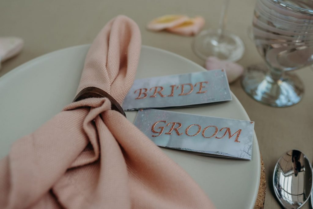 close up wedding tablescape pink napkin bride groom place cards