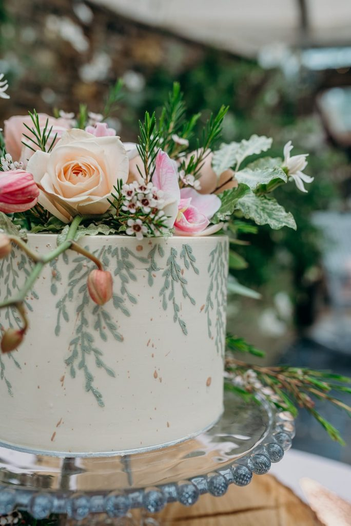 close up elopement cake painted ferns fresh flowers pink
