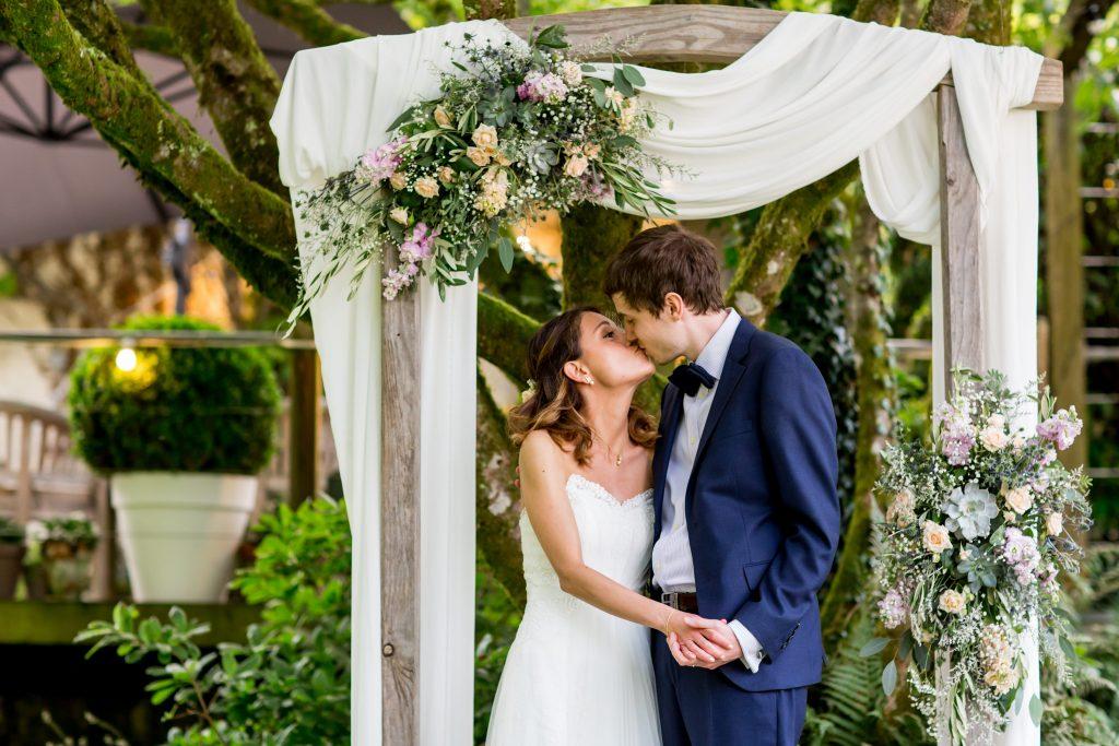 bride & groom kiss under floral arch