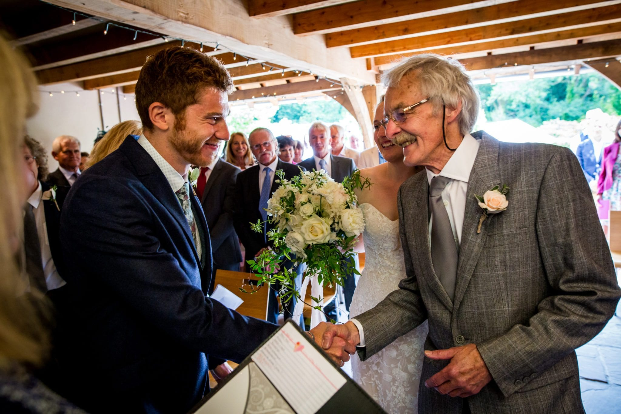 Father and groom handshake on the aisle