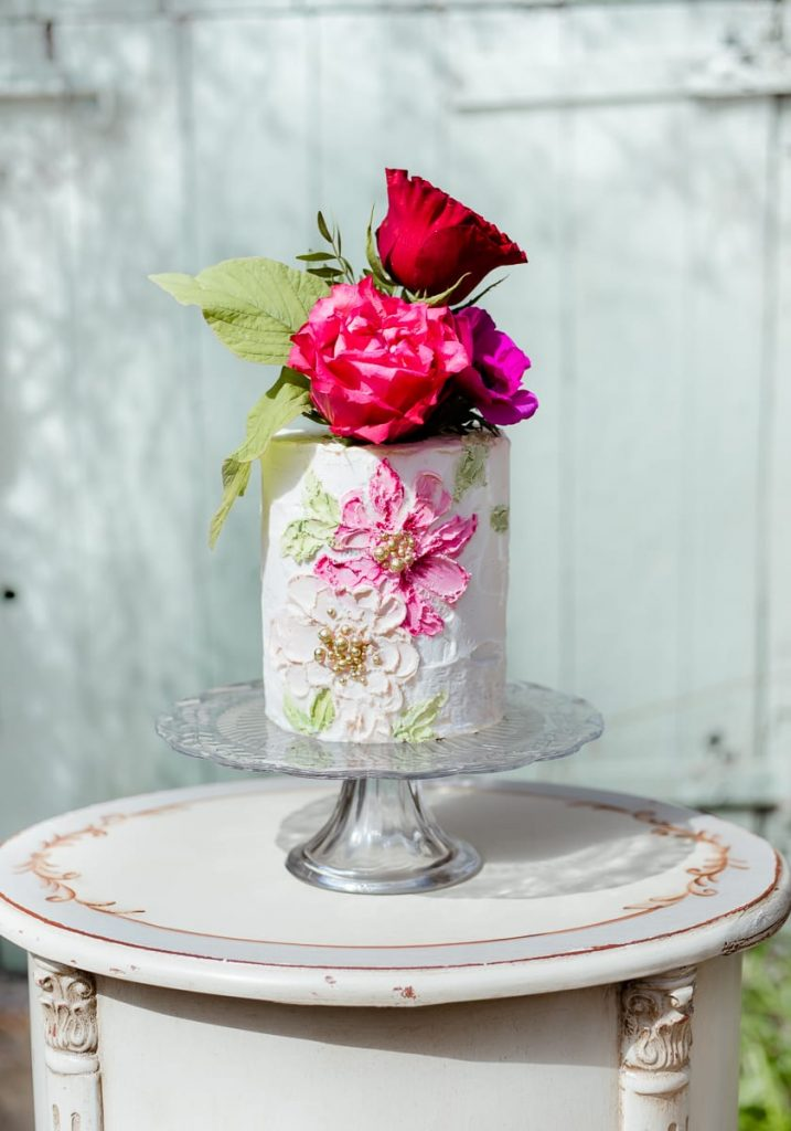 edible essence mini wedding cake on stand barn door pink flowers