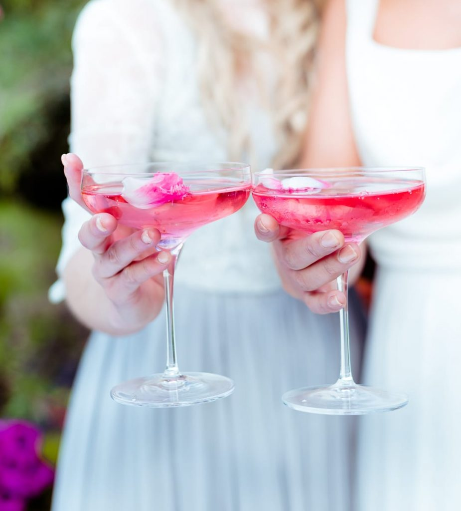 2 elopement brides holding pink cocktails